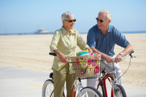 Couple posing on bikes at beach, California
