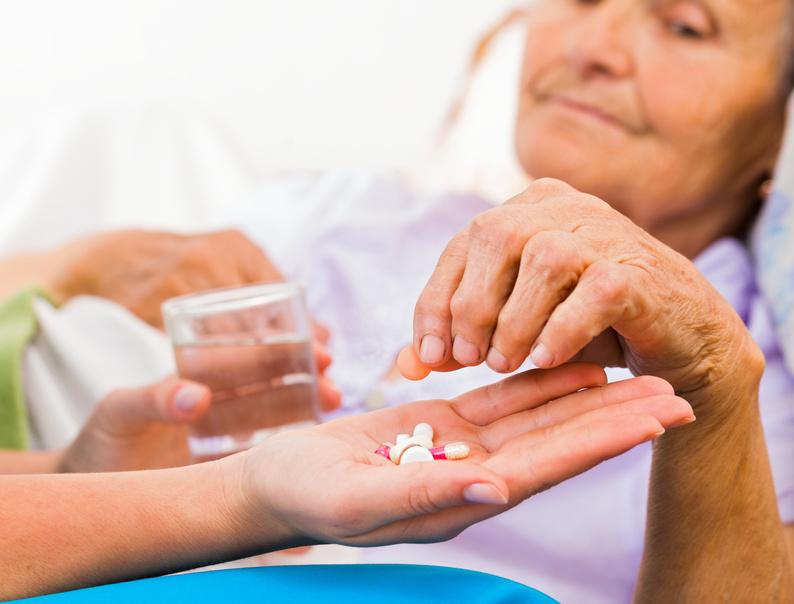 Homecare nurse helping elderly lady to take her daily medicine.